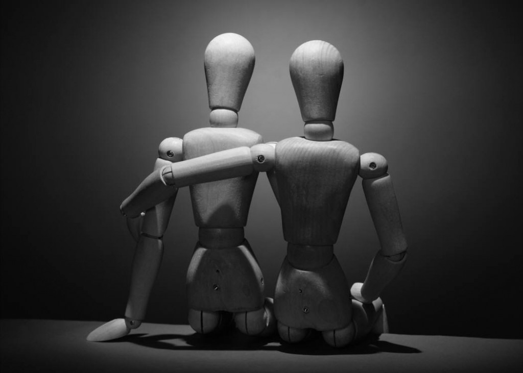image of two artists model dolls sitting side by side, one with its arm around the others shoulders.
